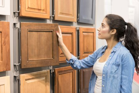 girl selecting kitchen cabinets